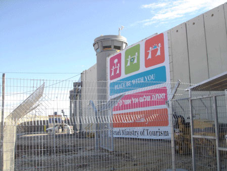 photo: large sign hangs on tall concrete wall with guard tower